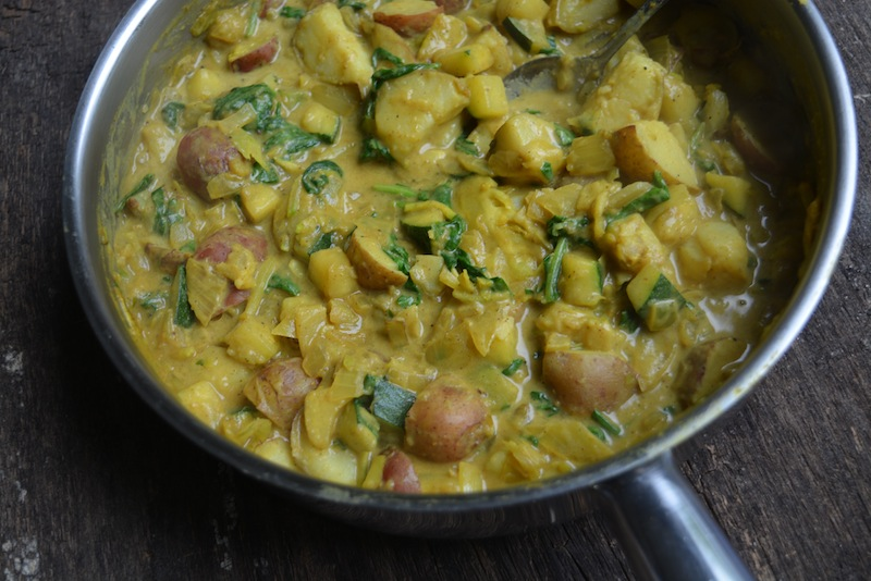 Potato curry with onions, spinach, zucchini and other vegetables